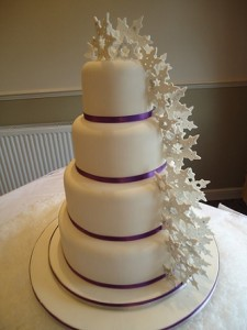 four tier purple ribbon wedding cake